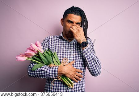 Young african american afro romantic man with dreadlocks holding bouquet of pink tulips smelling something stinky and disgusting, intolerable smell, holding breath with fingers on nose. Bad smell