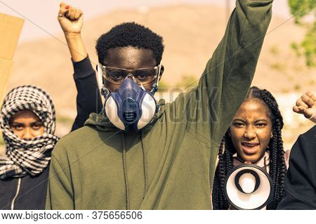 Portrait Of A Young Black Man With A Gas Mask, For Behind Two Young Different Ethnicity Women,