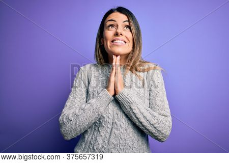 Young beautiful woman wearing casual sweater standing over isolated purple background begging and praying with hands together with hope expression on face very emotional and worried. Begging.