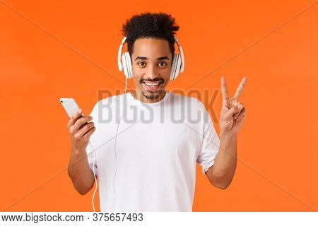 Peaceful And Friendly, Happy African-american Man In White T-shirt, Listen Music Headphones, Showing