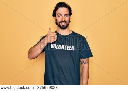 Young handsome hispanic volunteer man wearing volunteering t-shirt as social care doing happy thumbs up gesture with hand. Approving expression looking at the camera showing success.