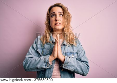 Young beautiful blonde woman wearing casual denim jacket standing over pink background begging and praying with hands together with hope expression on face very emotional and worried. Begging.