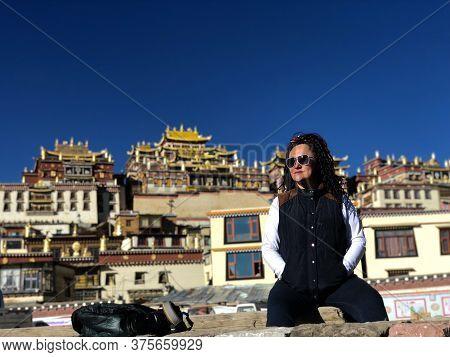 China, Tibet, Shangri-la, November, 2018 -   Woman Traveler Sitting On The Background Songzanlin Mon