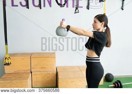 Side View Of Determined Latin Young Woman Exercising With Kettlebell At Gym