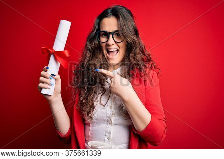 Young beautiful woman with curly hair holding university diploma degree over red background very happy pointing with hand and finger