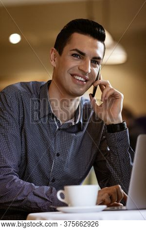 LGBTQ community lifestyle concept. Young homosexual man sits at the table in old-fashioned city cafe. Handsome smiling gay male businessman talks on a phone while having a break at lunch.