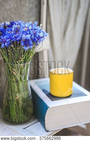 On The Balcony There Is A White Wooden Table With A Thick Book, A Yellow Cup Of Coffee And A Vase Wi