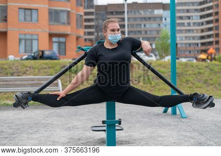 Overweight Young Woman In A Protective Mask Is Training On The Sports Ground. An Obese Girl Is Stret