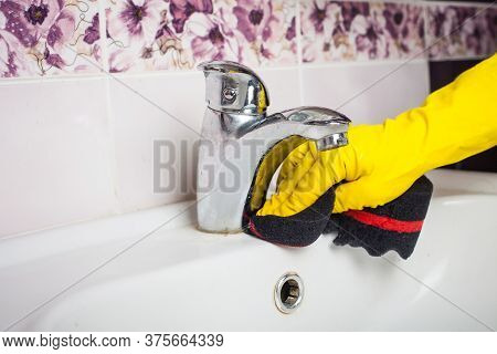 Maid With Rubber Glove Cleaning Tap And Sink.