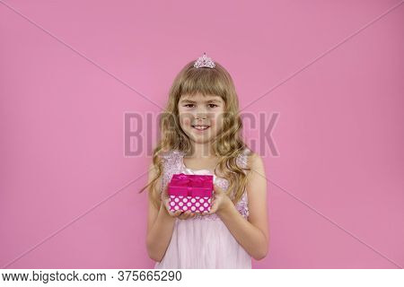 Little Girl On A Pink Background With A Gift. Little Girl S Birthday. Little Girl Holding A Gift In