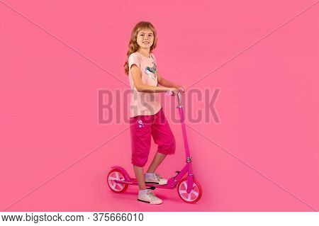 Little Girl With A Pink Scooter, On A Pink Background. Beautiful Girl In A Pink T-shirt And Shorts H