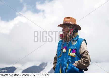 Vinicunca, Peru - October 29: Mountain Ranger In Uniform Observes Surrounding Landscape At Altitude