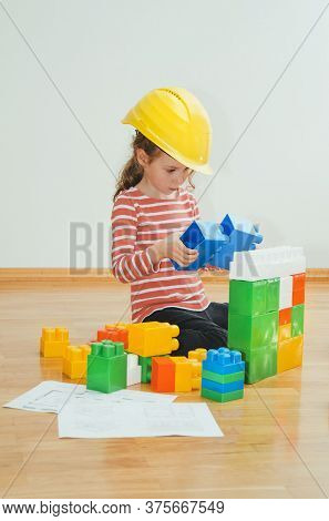 Little Girl With Yellow Hard Hat Playing With Constructor.