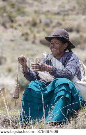 Copacabana,  Bolivia - November 7: Elderly Bolivian Woman Use Spindle To Form Thread Outdoors In Cop