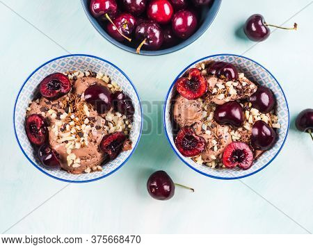 Two Chocolate Ice Cream Sundae With Cherries, Almond And Chocolate Sprinkles On Green Turquoise Back