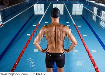 Professional Swimmer Is Wearing A Swim Cap And Swimming Shorts, He Standing In Front Of The Pool, Ba