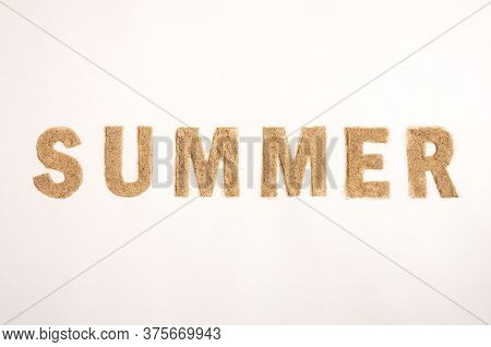 Word Summer Made Of Sand Isolated On White Background. Top View. Flat Lay