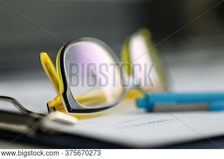 Close-up Stylish Reading Glasses Lie On Documents. Rest From Work During Quarantine. Maintain Excell