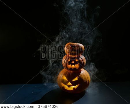 A Spooky Pyramid Of Jack-o-lantern In The Dark. Glowing Scary Smirk Carved In A Pumpkin. Traditional