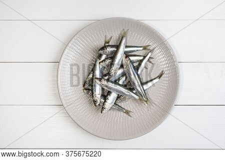 Some Sardines Arranged On A Plate On The White Wooden Table