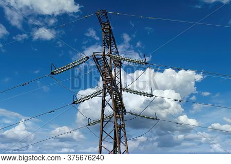 Transmission Line Of Electricity To Rural, High Voltage Electricity Pole On Bright Sky Background, E