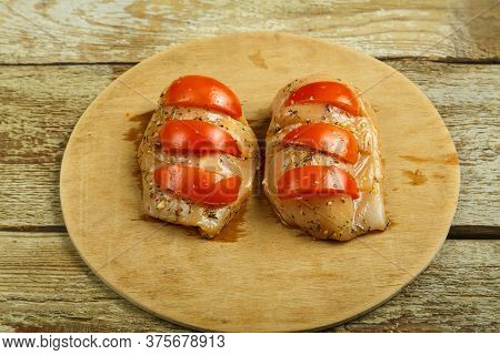 Marinade Chicken Breast Stuffed With Tomatoes On A Round Wooden Board.