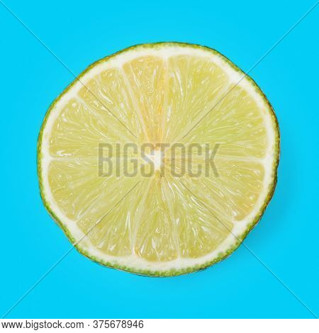 Slice of ripe lime isolated over cyan backround