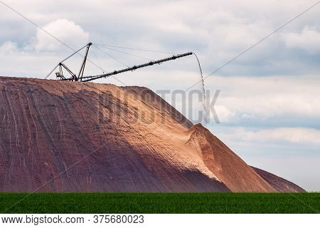 Extracting And Mining Potassium And Magnesium Salts.large Excavator Machine And Huge Mountains Of Wa