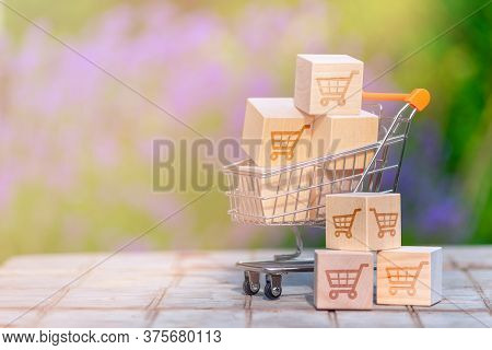 Shopping Online Concept - Parcel  With A Shopping Cart Logo In A Trolley On Wood Table Top. Shopping
