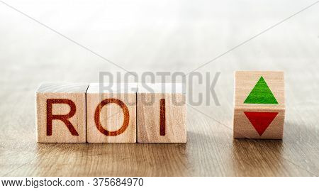 Roi Concept. Wooden Blocks With Roi Inscription And Block With Up And Down Arrows