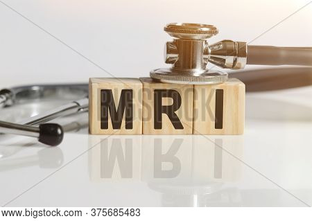 Mri The Word On Wooden Cubes, Cubes Stand On A Reflective White Surface, On Cubes - A Stethoscope. M
