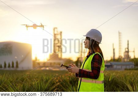 Asian Woman Engineer Operate Flying Drone Over Oil Refinery Plant During Sunrise Building Site Surve