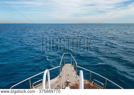 View From Yacht Bow To Sea Horizon. Blue Waves Of Red Sea. Way To Horizon. Cloudy Sky.