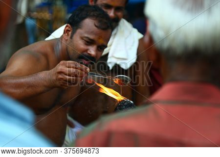 Kerala, India - December 20, 2019. An Indian Street Oil Vendor Adding Oil To The Fire In  Kerala, In