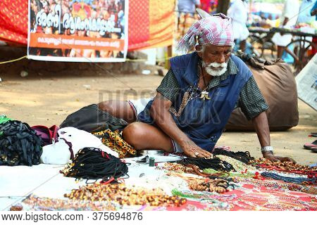 Kerala, India - December 20, 2019. An Indian Street Vendor Sitting With Colorful Beaded Necklaces In