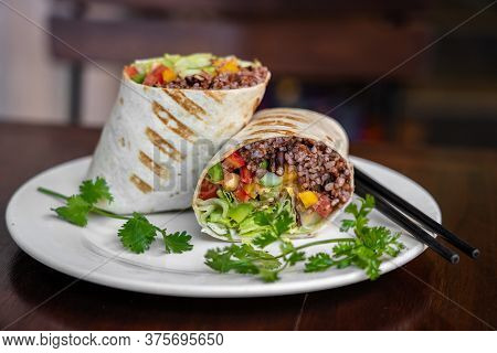Vegan Burrito. Sliced Up Raw Food Wrap With Vegan Ingredients On A Plate