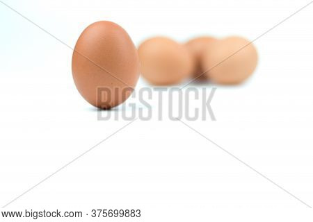Four Brown Eggs Separated From The White Background With Spaces For Writing Text.