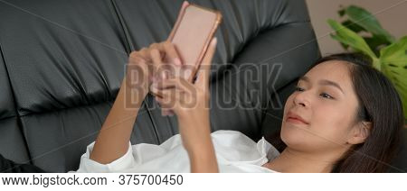 Cropped Shot Of A Woman Lying Down On Black Couch And Using Smartphone In Living Room On Day Off