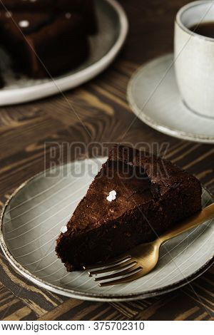 Moist Ginger Chocolate Cake Sliced And Sprinkled With Sea Salt And Cup Of Tea On Wooden Table. Selec
