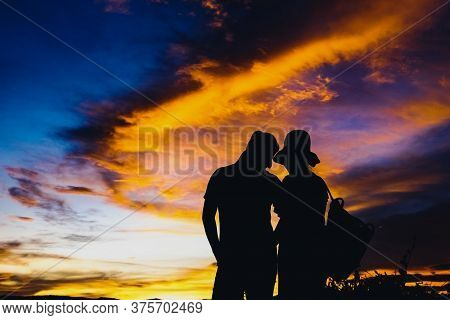 Silhouettes Couples With Sunset .