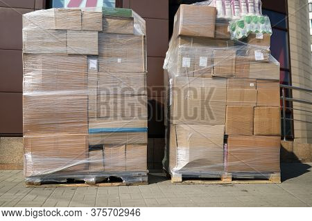 On City Street Are Pallets With Boxes In Film. Cardboard Boxes Are Used For Packaging Goods For Stor
