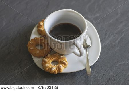 An Image With A Cup Of Coffee And Two Pretzels