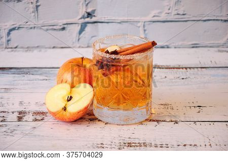 A Low Crystal Glass Of Cider With Cinnamon And Anise Stands On A Wooden Table, Next To Half And A Wh