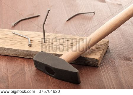 A Hammer And Bent Nails Dropped Near The Board, One Of The Nails Has Not Yet Fallen. Persistent Peop