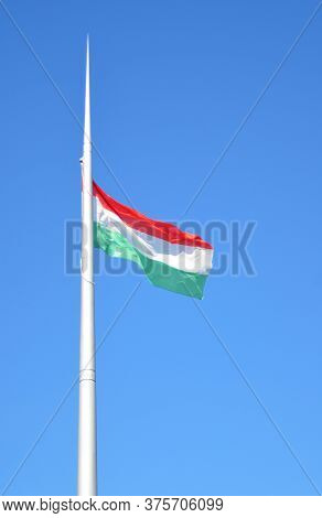 View Of The Spire With The Hungarian Tricolor Flag Flying Under The Blow Of Wind In Clear Sunny Weat