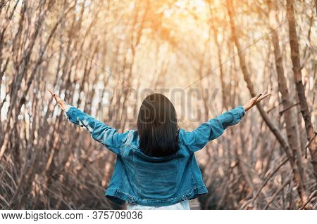Woman Raise Hand Up In Forrest With Sunlight Ray Abstract Background. Freedom Feel Good And Trave Ho