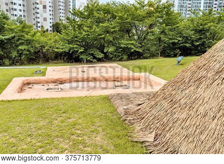 Concrete Impressions Of Ancient Structures Behind Straw Hut At Prehistoric Archeological Site In Dae