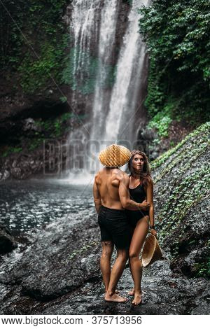 A Man And A Woman In Conical Hats At A Waterfall. A Couple In Love On A Waterfall. A Beautiful Girl