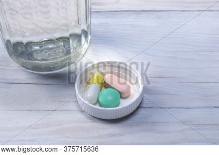 Daily Doses Of Tablets For Patients On Wood Table