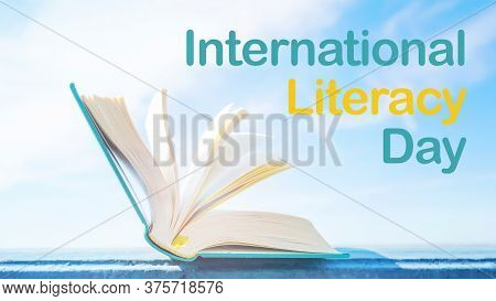 International Literacy Day. An Open Book With A Green Cover Against The Sky. Bright Light Banner. Ye